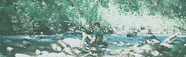 イルビゾンテの財布を持って水場でキャンプを楽しむ男性