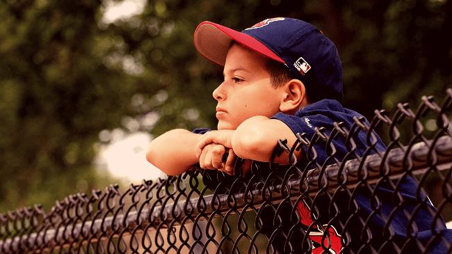 グランドを見つめる野球チームに入りたい子供
