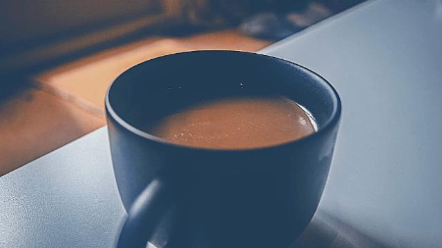 職場で淹れたばかりのコーヒーが入ったマグカップ