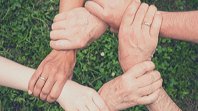 家族がお互いの手を握り合って支え合っているイメージ