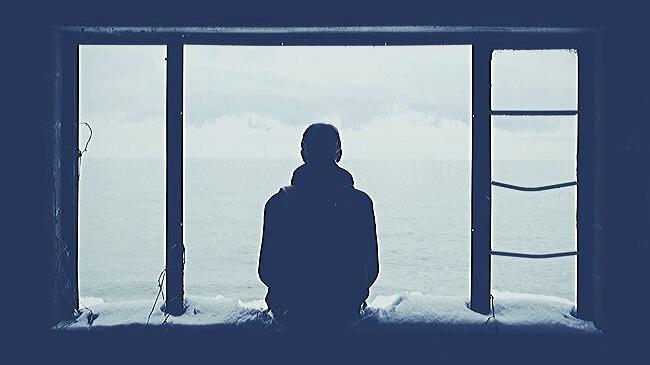 遠く海を眺めながら物思いにふける人