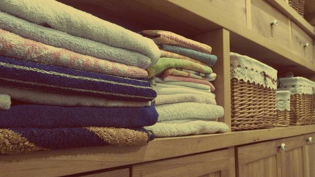 脱衣場にきれいに畳まれたフェイスタオルとバスタオル