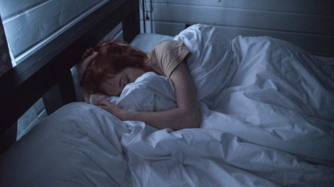 寝る前のスマホをやめて、ぐっすり寝ている女性