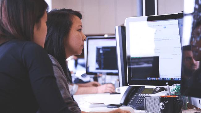同僚にメールの誤送信を防ぐために確認してもらっている女性社員