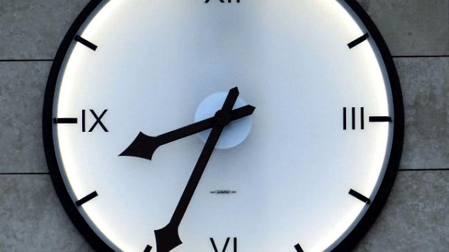 満員電車が行き交う駅の時計