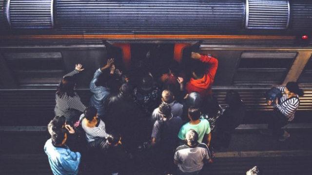 通勤で満員電車に乗ろうとするサラリーマン