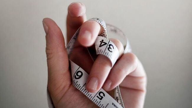 30代男性が持っているウエストを測るためのメジャー