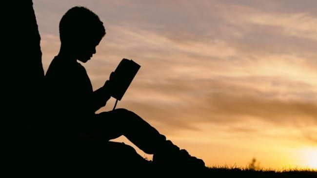 外で気持ちよさそうに本を読む子供