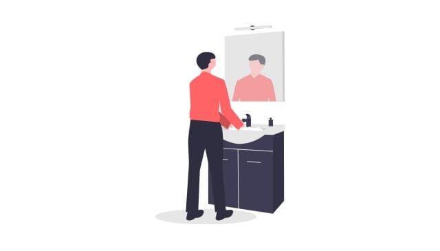 新入社員が鏡で自分の身だしなみをチェックしている様子